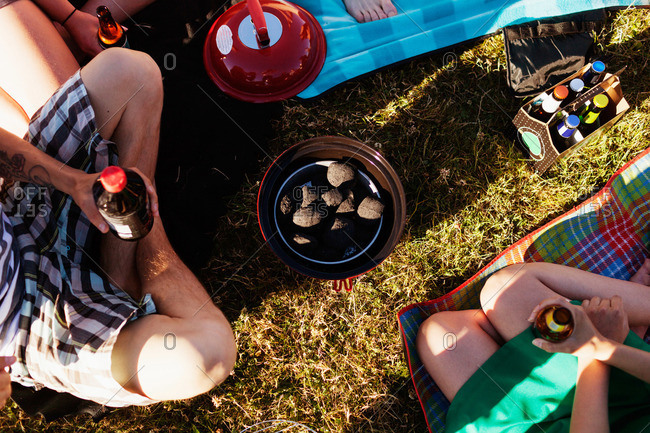 Overhead view people around of small barbecue grill on grass at a picnic
