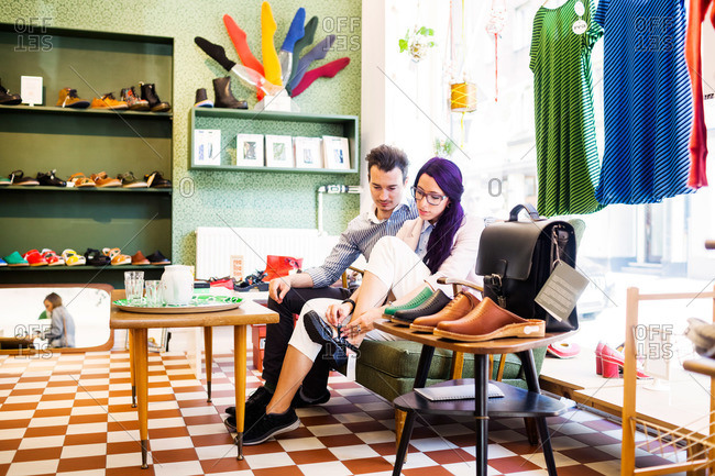 Man watches woman try on shoes in boutique