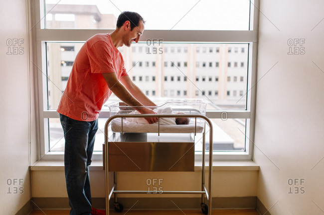 Father adjusting his newborn daughter in a hospital bassinet