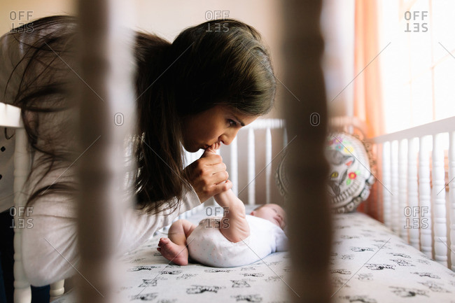 Mother kissing her newborn daughter's feet in a crib