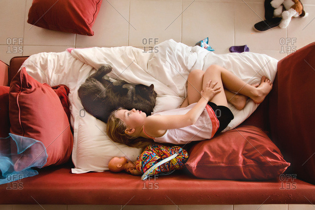 Girl looking cuddling on the couch with her cat