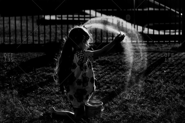 Girl spraying water in sunlight