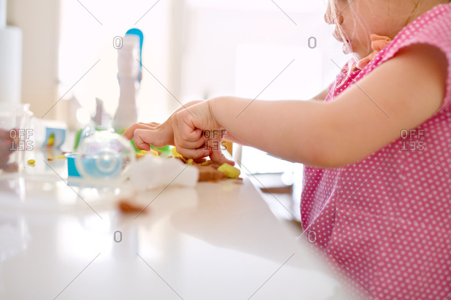 Young girl playing with her food