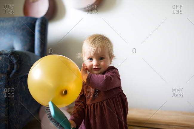 Toddler girl holding balloon and brush
