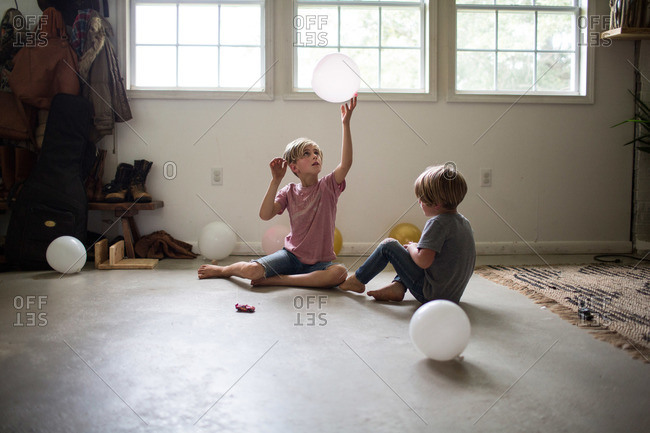 Boys sitting on floor playing with balloons