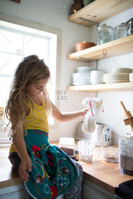 Girl in apron using a cheesecloth