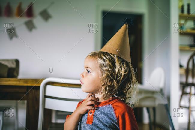 Toddler boy touching neck wearing party hat