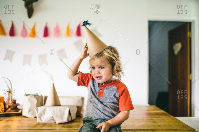 Boy on table annoyed at party hat