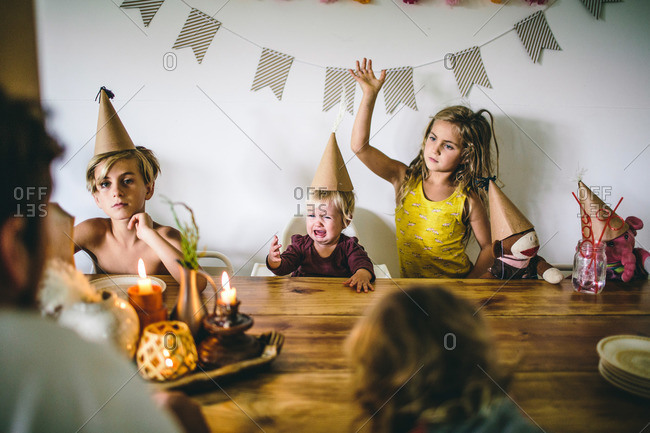 Family in party hats with crying toddler