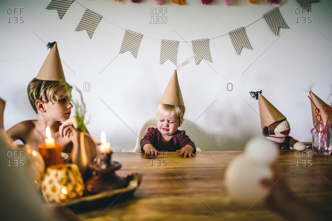 Upset toddler and family in party hats