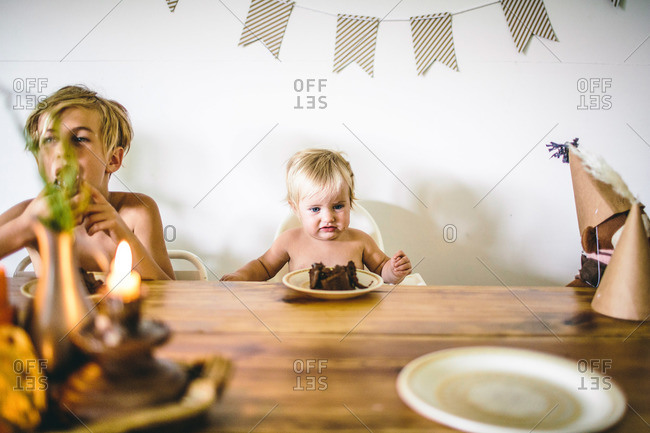 Two kids eating cake at birthday table