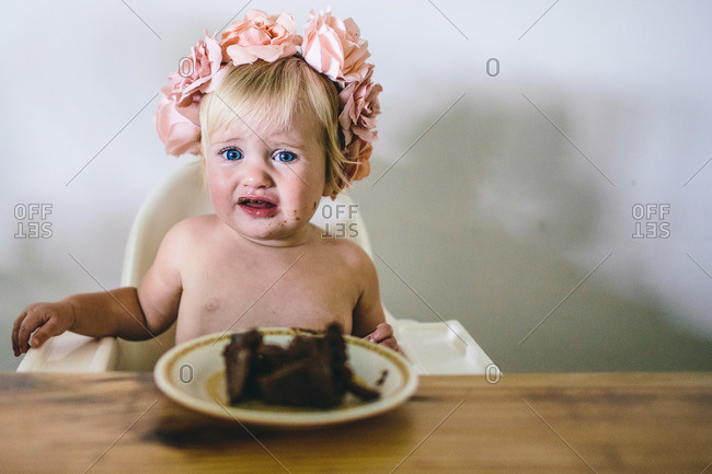 Toddler in flower crown with birthday cake
