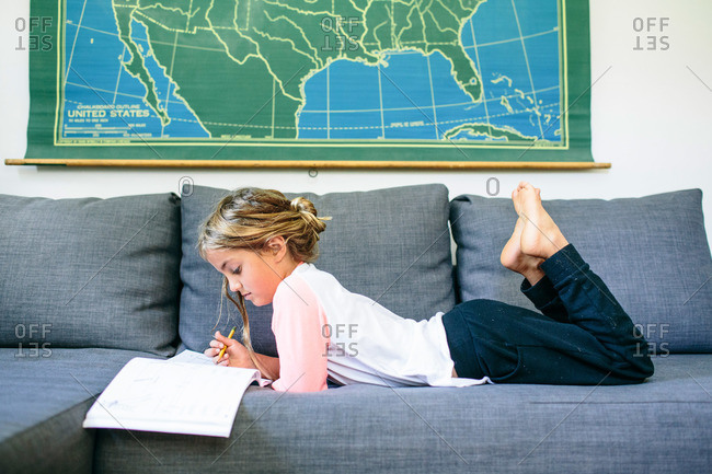 Girl writing in book lying on the couch