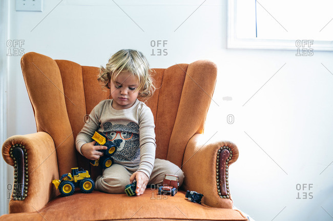Toddler boy playing with trucks in armchair