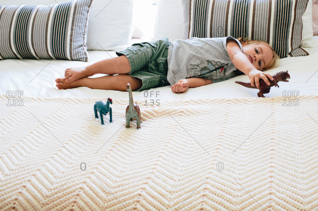 Toddler boy lying on bed with toy dinosaurs