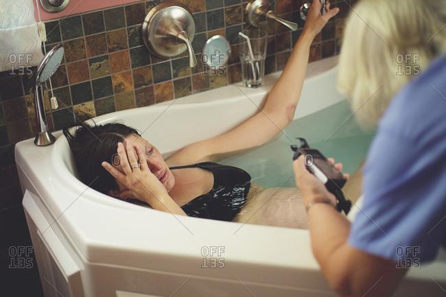 A woman in labor lays in a bathtub