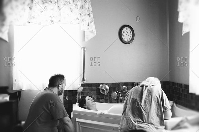 A husband sits by his expectant wife in a hospital room
