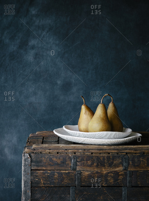 Pears sitting on a white dish on top of a wooden trunk off center