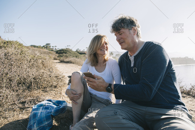 Middle-aged couple with smartphone at the coast
