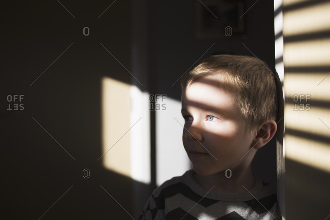 Little boy standing in shadows from window blinds
