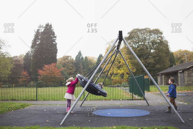 Little boy swinging at a park with two other kids