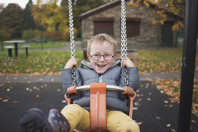 Little boy swinging at a park