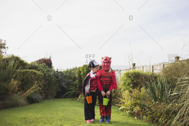 Two little boys standing together in their Halloween costumes