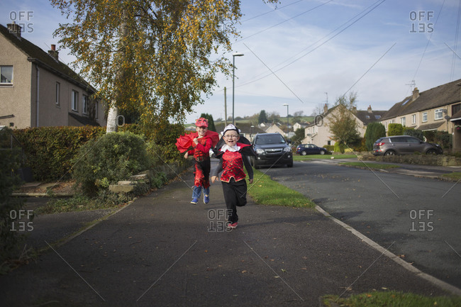 Two little boys running together in their Halloween costumes