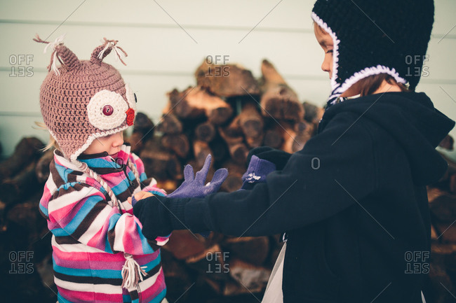 Girl helping another put on winter clothes