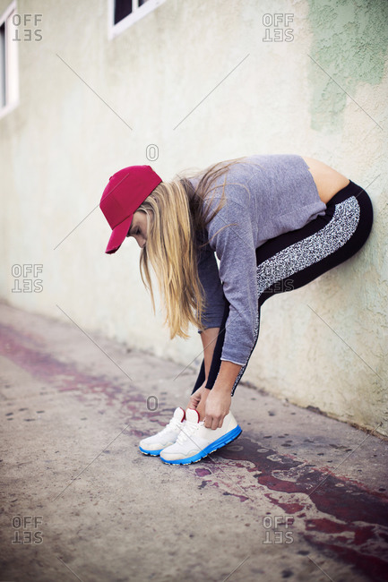 Young woman in red hat bent over tying her shoelaces