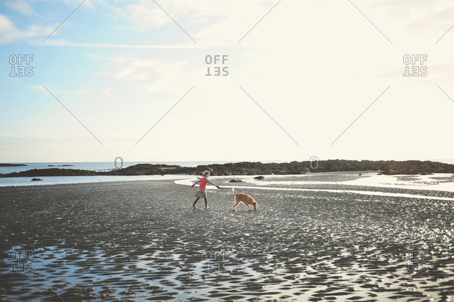 Girl walking dog on cold beach