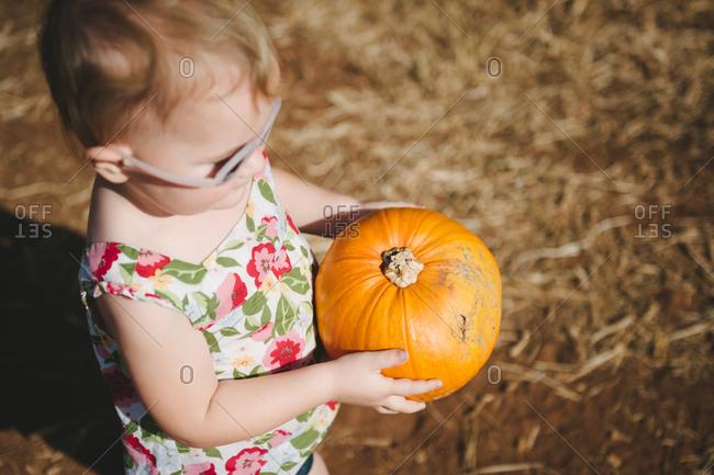 Toddler girl holding ripe pumpkin