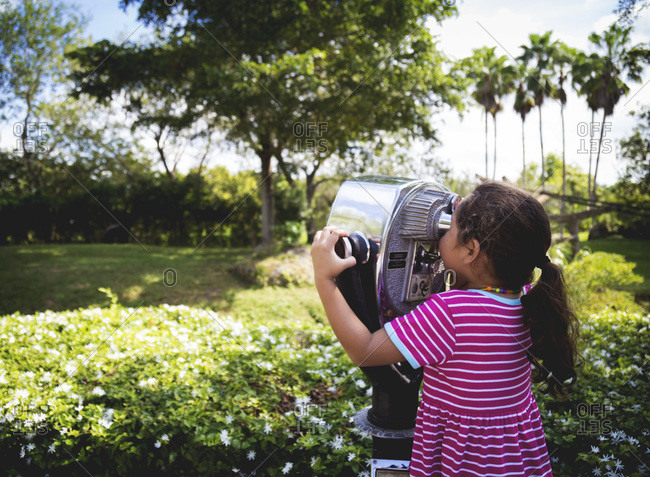 Girl looking through coin-operated binoculars