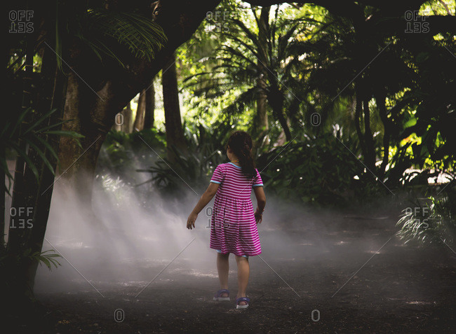 Girl walking through a humid tropical garden