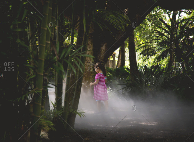 Girl walking through a steamy tropical garden