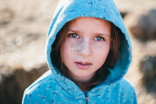 Portrait of little girl in a blue jacket with her hood up
