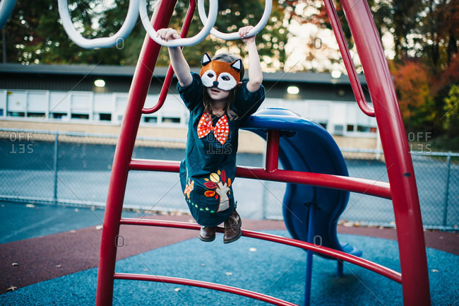 Young girl dressed up as a fox while skipping down a path