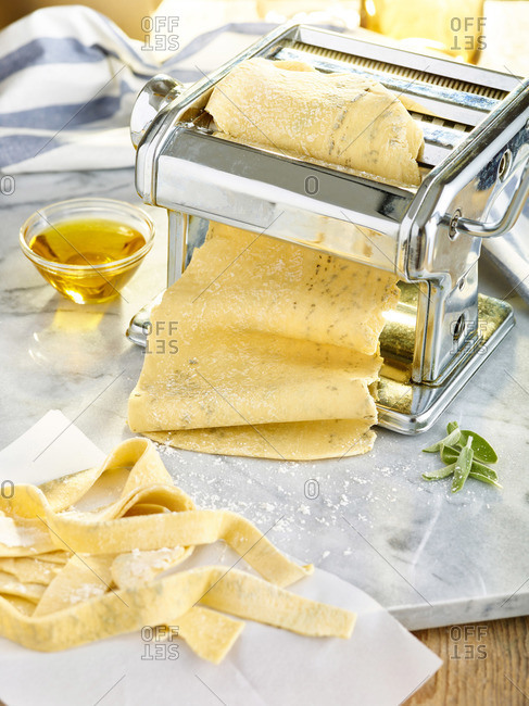 Making herbed pasta in a hand-cranked pasta machine