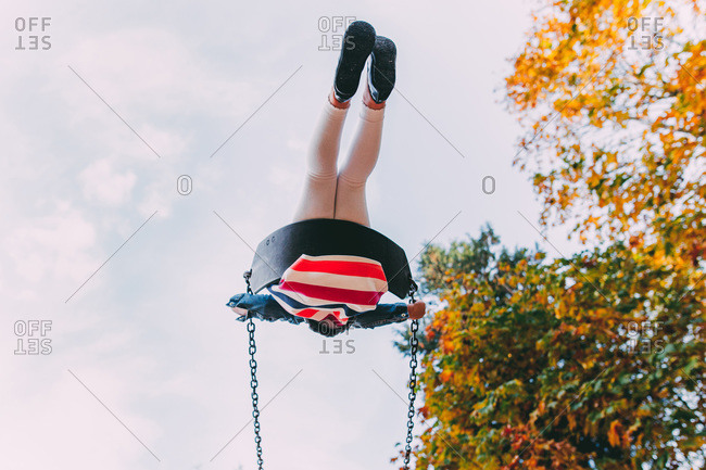 d62499075c64 View from below a girl on a swing stock photo - OFFSET