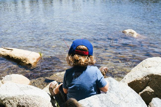 Rear view of little boy fishing on rocks