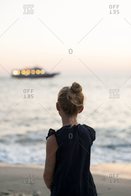 Back view of young girl on beach watching a boat in the ocean at sunset