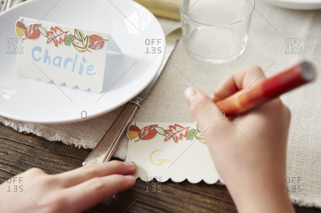 Child writing names on place cards for a dining table