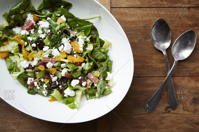 Spinach salad with dried fruit, cheese and fruit