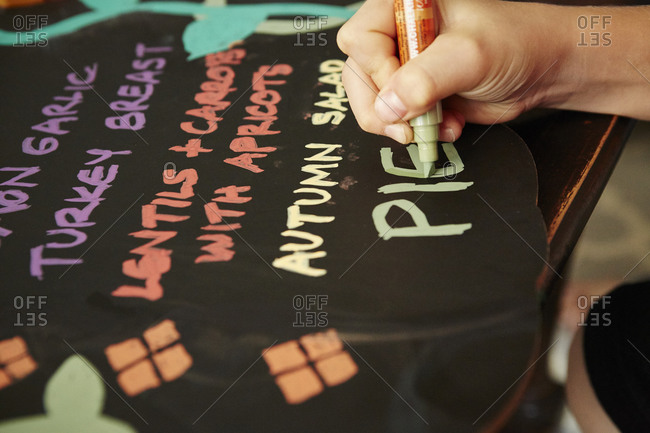 Child\'s hand writing a Thanksgiving menu on a chalkboard
