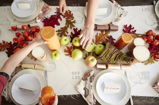 Hands holding decorations on a Thanksgiving table