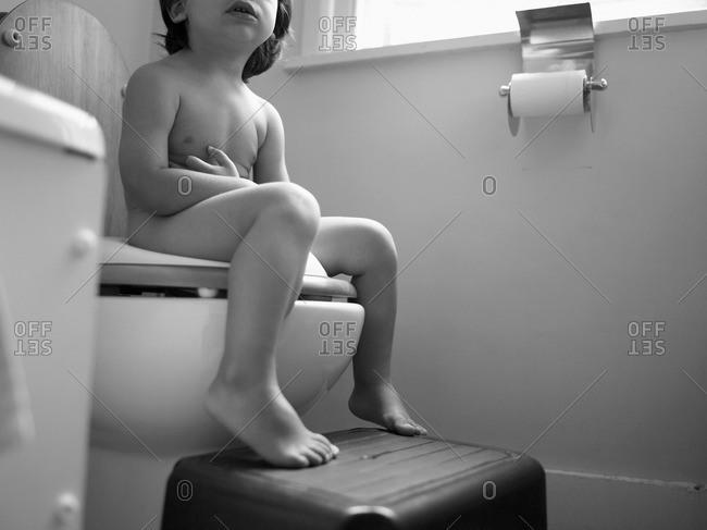 Child Sitting on Toilet