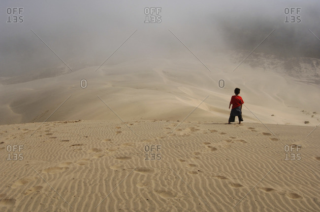 Boy Standing on Sand Dunes, Siuslaw National Forest, Oregon, USA