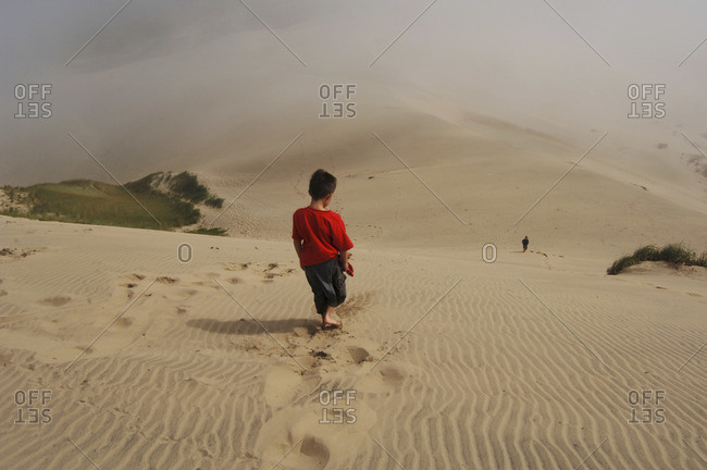 Boy Walking on Sand Dunes, Siuslaw National Forest, Oregon, USA