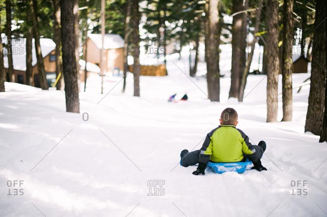 Boy sledding down a hill in winter