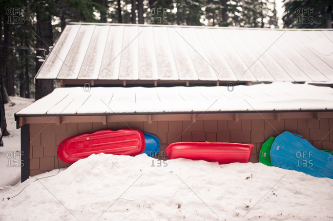 Sleds stacked up against a cabin exterior wall